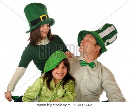 A father and his daughters celebrating St. Patrick's Day wearing green and giant-sized hats.  Isolated on white.