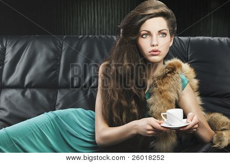Young Elegant Girl In Green With Cup, She Is In Front Of The Lens But She Looks At Left.