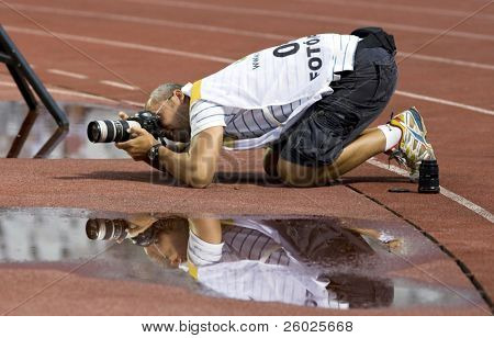 BUDAPEST, HUNGARY - AUGUST 12: Press photographer taking photographs at a friendly soccer match between Hungarian National Team and Romanian National Team on august 12, 2009, Budapest, Hungary.