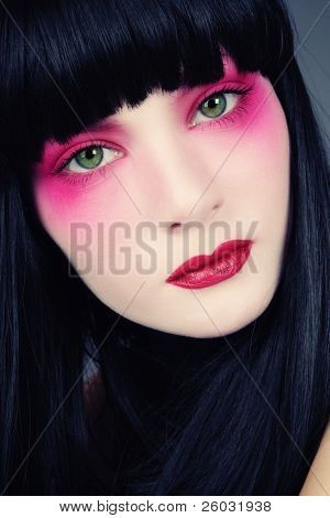 Portrait of young beautiful green-eyed brunette with fancy pink make-up