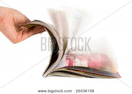 Hand which is thumbing magazine. Isolated on white