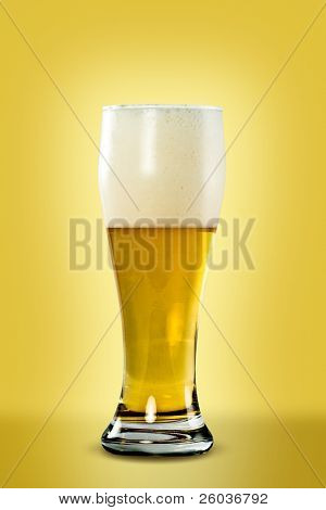 Glass of light beer with foam on yellow background