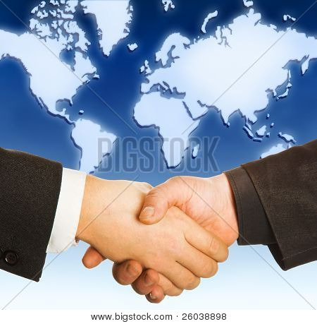 Hands shake with map of the world in background