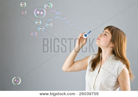 Young beautiful girl blow out soap bubbles on gray background