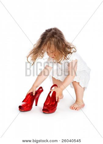 Little girl in white dress with big red shoes. Isolated on white background