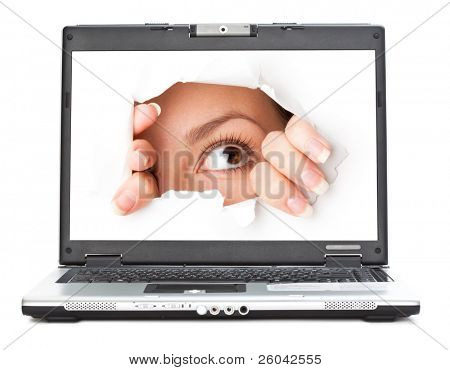 Eye looking through hole in screen of laptop. Isolated on white background