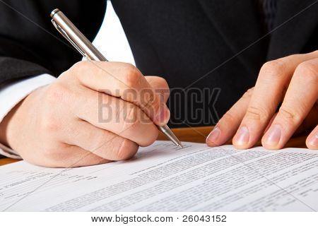 Cerca de una manos de empresario firmar un contrato. Aislado sobre fondo blanco