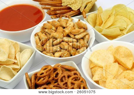 Salty snacks and salsa dip sauce in white bowls