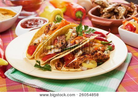 Chicken and vegetable salad served in taco shells