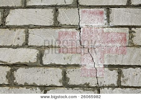red Cross on the brick wall with a crack