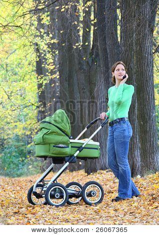 Mother and baby in the autumnal park.  Mother is speaking on the phone.
