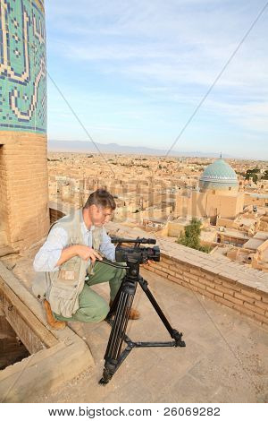 Cameraman in ancient city of Yazd, Iran - shooting from the mosque top (focus on city background)