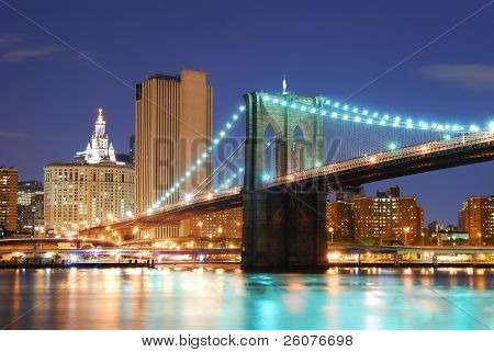 New York City Manhattan skyline and Brooklyn Bridge at dusk over Hudson River with skyscrapers