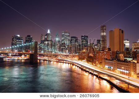 New York City Manhattan skyline and Brooklyn Bridge with skyscrapers over Hudson River illuminated with lights and busy traffic at dusk after sunset.