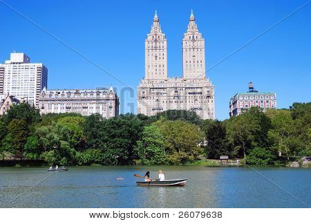 New York City Central Park with Manhattan skyline skyscrapers and blue sky with boat in lake.