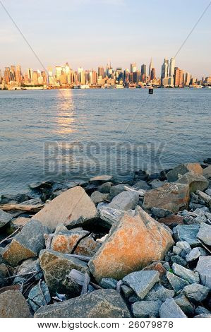 New York City Manhattan midtown skyline at sunset with reflection over skyscraper and river viewed from New Jersey Hudson River Shore with rocks.
