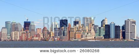 New York City Manhattan downtown district skyline panorama with skyscrapers over river with blue clear sky.