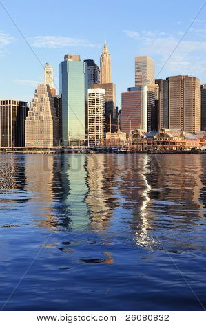 Lower Manhattan skyline panorama over East River with reflection and blue sky in New York City