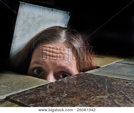 A young woman's eyes and forehead appearing from beneath a tile tabletop.