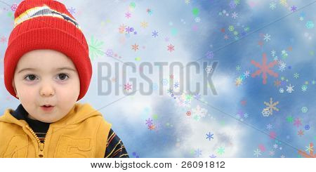 Toddler boy against a magical snow storm with space for copy.