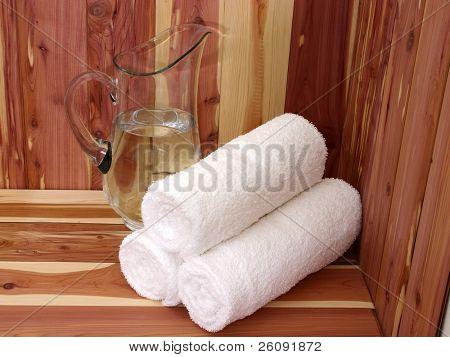 weiße Handtücher und Krug Wasser auf einer Zeder-Bank.