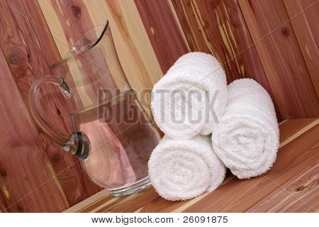 White towels and pitcher of water scrub on a cedar bench.