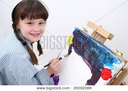 Adorable grade school aged girl painting.