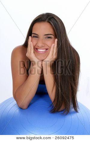 Beautiful dark haired tan teen girl in workout clothes leaning on excercise ball.