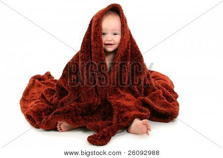 Beautiful 10 Month Old Baby Wrapped In Brown Fuzzy Blanket. New baby teeth showing. Shot in studio over white.