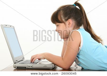 Child laying down working on laptop.  Shot in studio over white. Casual school clothes.