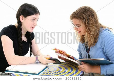 Two 12 year old girls doing homework together. Shot in studio over white.