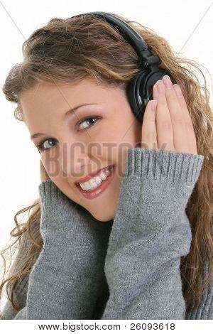 Beautiful sixteen year old teen girl listening to headphones. Shot in studio over white.