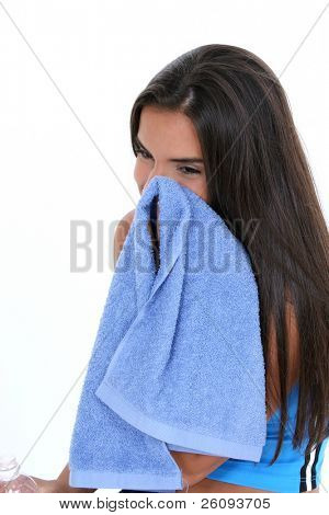 Teen girl in workout clothes with bottle of water, wiping face with towel. Shot in studio over white.