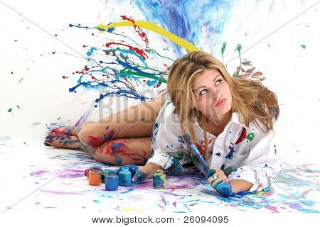 "Beautiful young woman laying in paint covered studio.  Paint splattered on walls, floor, model.  Shot in studio over ""white"".  :)"