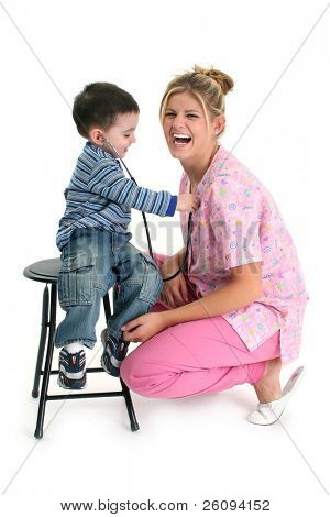 Toddler boy listening to nurse's heart with stethoscope.  Shot in studio.