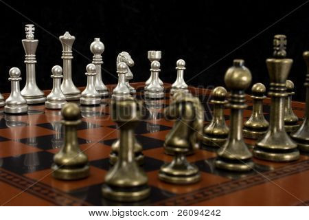 Wooden chess board with metal peices.  Shot in studio on black from corner to corner.  Focus on light pieces.