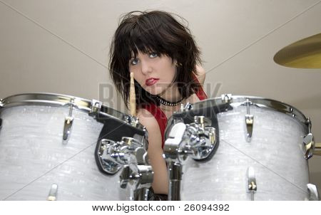 Beautiful teen girl in red vinyl dress and dog collar sitting at drum set.