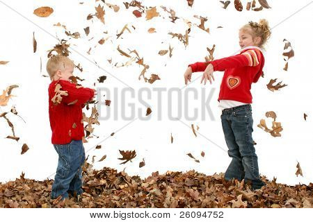 Happy two year old boy and five year old sister throwing leaves at each other.