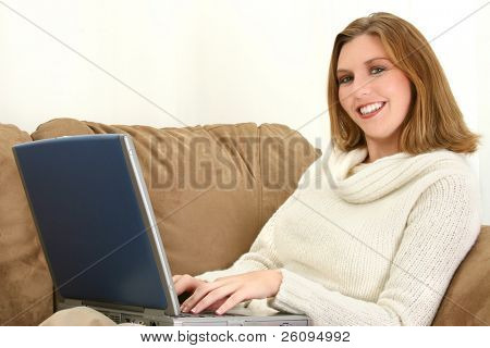 25 year old woman on the couch working on a laptop computer.  Wearing cream sweater, smiling.