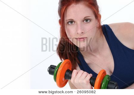 17 year old girl with long red hair over white holding hand weights