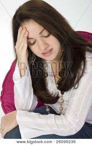 Beautiful young woman sad or with headache.  Shot in studio.