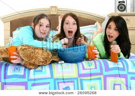 Three teen girls eating and watching television at home.