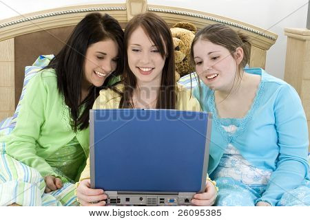 Three teen girls smiling at laptop.