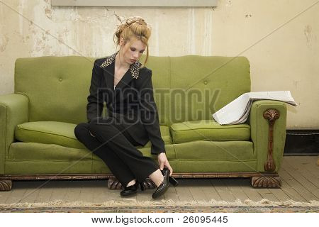 Beautiful young Hispanic business woman in suit removes shoes in her impoverished home.  Conceptual for working to