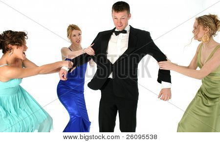 Three beautiful young woman in formal dresses fighting over handsome man in tuxedo. Shot in studio over white.