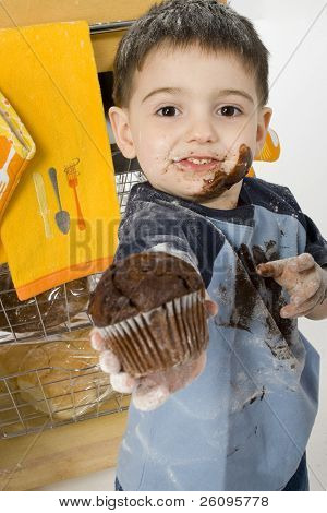 Three year old boy handing chocolate chip muffin to camera.  Covered in chocolate and flour.