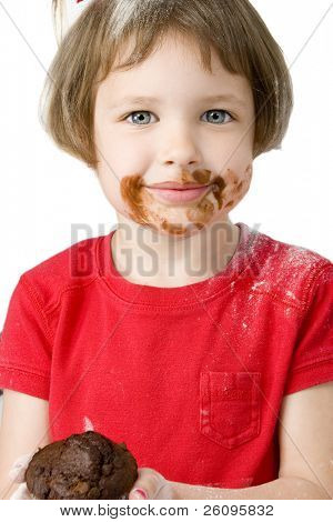 Beautiful four year old girl covered in flour and chocolate, holding chocolate chip muffin. Shot in studio over white.