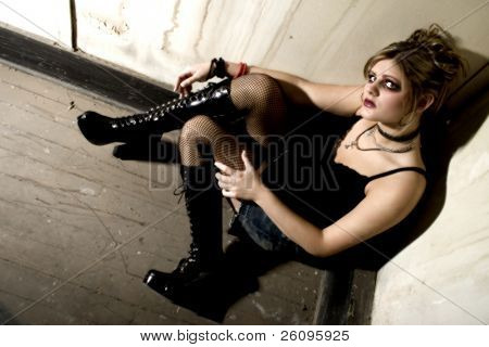 Goth girl in corner of old grundgy building.