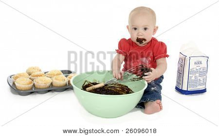 Baby girl with mixing bowl, chocolate batter, flower and muffins.