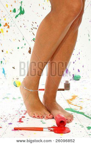 Sexy pair of legs in paint in paint splattered studio.